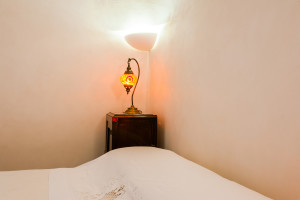 Un angolo illuminato della stanza da letto Carrubo nel trullo di Tre Casiedde
