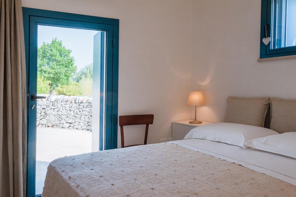 Un angolo della camera Lavanda, con la porta blu che si affaccia sulla veranda